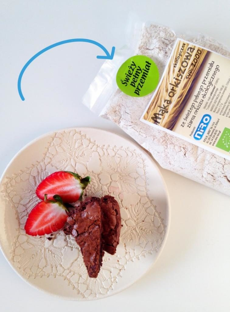 brownie z truskawkami na talerzyku, obok pełnoziarnista mąka orkiszowa NIRO Bio